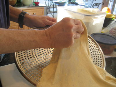 Pull pizza dough onto lightly oiled perforated disk