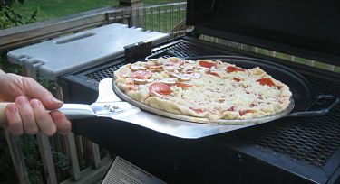Slide pizza onto grill with aluminum peel